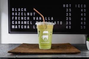 Matcha Ice Latte auf einem brauen Tablett mit dem Kaffeeangebot des Beanbrewing Cafés im Hintergrund