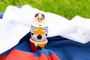 Matroschka mit einem Fußball auf russischer Flagge