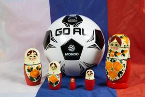 Matryoshka dolls standing around soccer ball on Russian flag