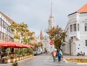 Matthiaskirche in Budapest mit einem Restaurant und spazierenden Touristen im Vordergrund