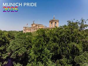 "Maximilianeum behind green trees and blue sky with the picture title ""Munich Pride 2025"" in rainbow-colors, for the Christopher-Street-Day Festival"