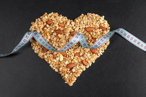 Measuring tape on a heart made of oatmeal with almonds on a black background. Nutritional concepts