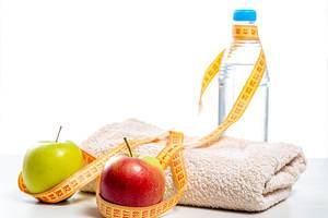 Measuring tape wraps around a bottle of clean water, apples and a towel. Sports concept, healthy lifestyle