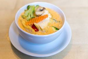 "Meatless and hot spicy coconut milk soup ""Tom Yum"" with tofu and fresh vegetables, in a white soup bowl, as a vegan starter"