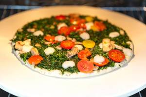 Meatless pizza Verdura by Trattoria Alfredo with spinach, yellow tomatoes and mushrooms in the oven on a pizza stone by BBQ Premium