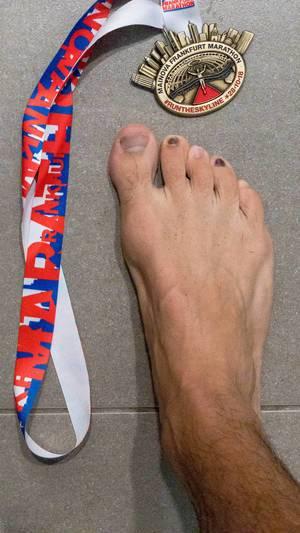Medaille des Mainova Frankfurt Marathon 2018 auf Fliesenboden mit einem Fuß