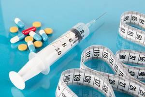 Medical syringe, pills and tape measure on blue background