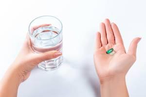 Medikamente einnehmen - Frau hat grüne Tablette in Handfläche und hält mit anderer Hand Wasserglas