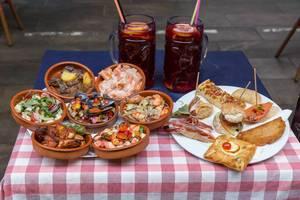 Mediterrane Delikatessen mit Muscheln, Shrimps, Gemüse und spanisches Brot mit Schinken vor roten Drinks auf einem kleinen Tisch in Barcelona