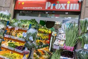 """Mediterranean fruits and vegetables at the Spanish supermarket """"Proxim"""" in a corner shop style at the street Carrer de Joaquín Costa in Barcelona"""