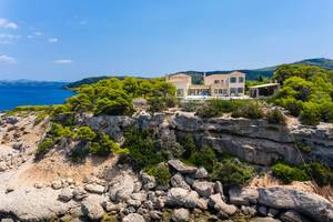 Mediterranean villa with pool surrounded by nature, on a rocky cliff of the Greek island Spetses
