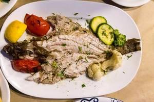 Mediterraner Teller mit ganzem frischem Fisch, Zitrone und gekochtem Gemüse