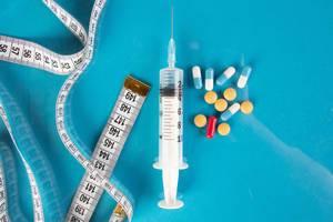 Medizinische Spritze mit bunten Pillen, Tabletten und Maßband auf blauem Hintergrund