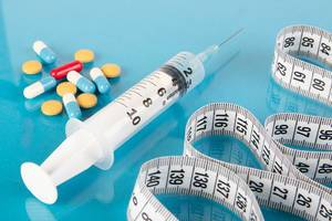 Medizinische Spritze, Tabletten, bunte Kapsel und ein Maßband auf blauem Hintergrund