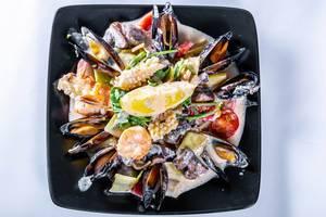 Meeresfrüchte wie Muscheln Tintenfisch angerichtet mit Soße auf schwarzem Teller vor weißem Hintergrund