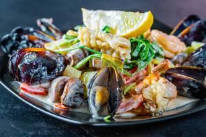 Meeresfrüchte wie Muscheln und Shrimps mit gegrilltem Gemüse und Zitrone in cremiger Soße