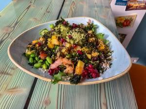 Meeresfrüchtensalat mit Mango, Bohnen, Reis mit kerniges Topping auf weiß-blauem Teller im Nahaufnahme
