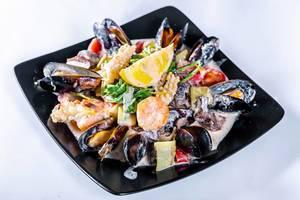 Meeresfrüchtesalat mit Crevetten, Muscheln, Oktopus und Gemüse an leckerer Soße
