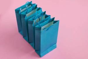 Mehrere blaue Geschenktüten vor einem rosafarben Hintergrund