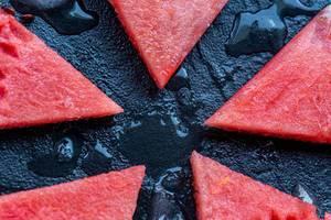 Mehrere dreieckige Wassermelonen-Stücke liegen auf einem schwarzen Stein