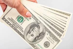 Mehrere einhundert Dollar-Scheine in einer Frauenhand vor weißem Hintergrund