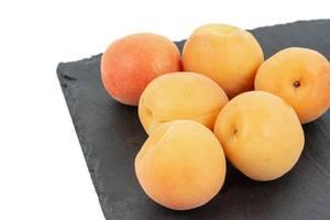 Mehrere, gereifte Aprikosen liegen als Sommerobst auf einer schwarzen Steinplatte