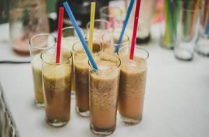 Mehrere Gläser mit Kiwi Milchshake Smoothies mit bunten Trinkhalmen auf weißem Tisch
