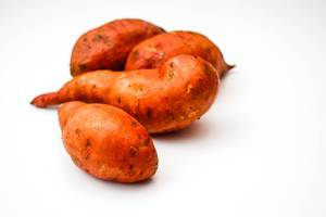 Mehrere Süßkartoffeln vor weißem Hintergrund