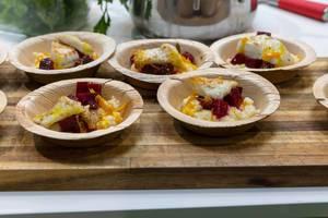 Mehrere Teller mit Fisch mit Gemüse und roter Bete als Ergebnis eines Showkochens