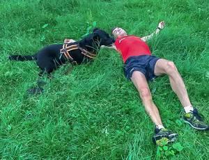 Mein Schwarzer Labrador und ich liegen im Gras