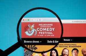Melbourne International Comedy Festival logo on a computer screen with a magnifying glass