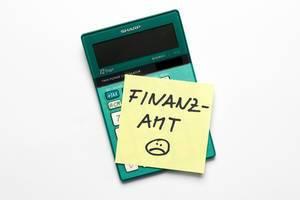 Memo Zettel mit dem Wort Finanzamt auf einem Taschenrechner