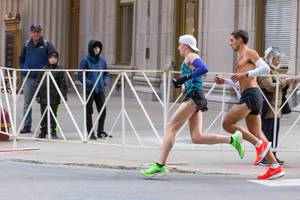 Men and male participants of Chicago marathon running shirtless through the streets