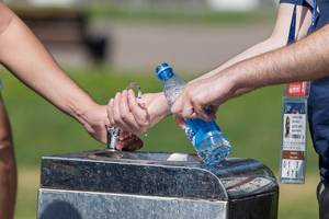 Men filling a plastic bottle with water at a drinking fountain
