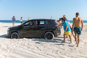 Men pushing a stuck SUV on a beach