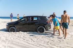 Men pushing a stuck SUV on a beach