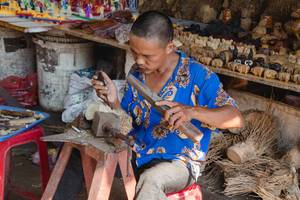 Men sculpting wood at the  Marke Vietnam. (Flip 2019)