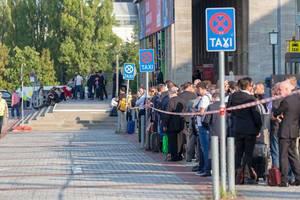 Menschen am Messegelände warten auf Taxis
