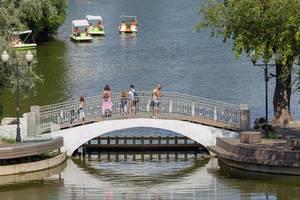 Menschen auf kleiner Brücke schauen Leuten in Tretbooten zu