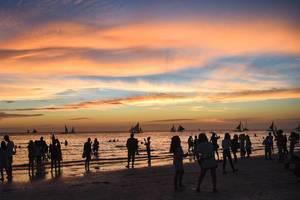 Menschen genießen den Sonnenuntergang zur goldenen Stunde am Strand von Boracay, Vishayas, Philippinen