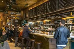 Menschen im Café mit Bäckerei-Theke im Altbaustil in Barcelona, Spanien