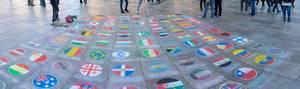 Menschen legen Münzen auf Ländeflaggen mit Kreide auf Pflaster gemalt  auf dem Kölner Weihnachtsmarkt