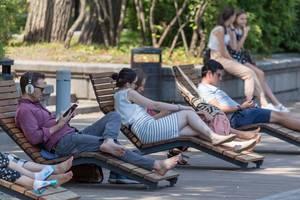 Menschen liegen auf Liegestühlen aus Holz