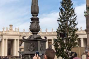 Menschen machen Fotos vom Angelus auf dem Peterplatz im Vatikan