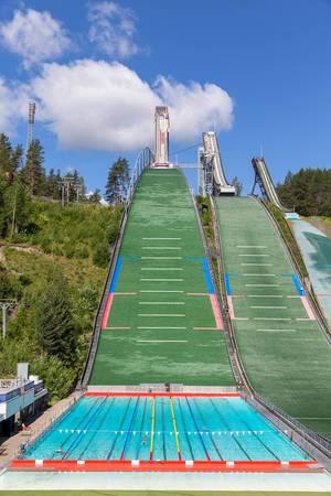 Menschen schwimmen Bahnen im einzigartigen Schwimmbad, am Fuß der Salpausselkä-Sprungschanze, während der Sommersaison in Lahti