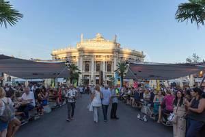 Menschen sitzen im Open-Air-Restaurant am Rathausplatz, Burgtheater im Hintergrund