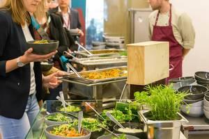 Menschen stehen in der Schlange vor dem ausgewogenes Mittagessen mit Salatbar am Büfett des Barcamps OMWest19 von AXA in Köln
