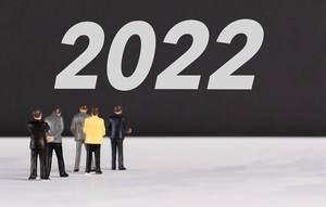 """Menschen stehen vor dem Text """"2022"""""""
