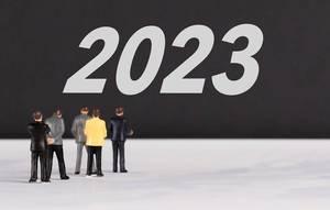 """Menschen stehen vor dem Text """"2023"""""""