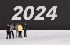 """Menschen stehen vor dem Text """"2024"""""""